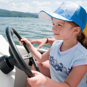 little girl piloting boat