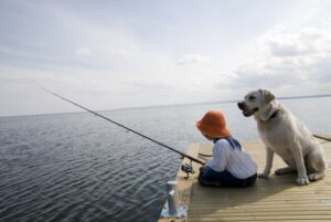 Boy fishing with his dog on a dock