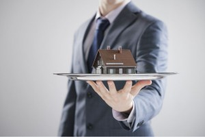 man holding a tiny model of a house on a silver platter