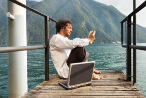 man reading on lake with laptop