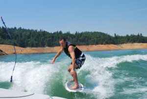 man riding a wakesurf board behind a boat on the lake