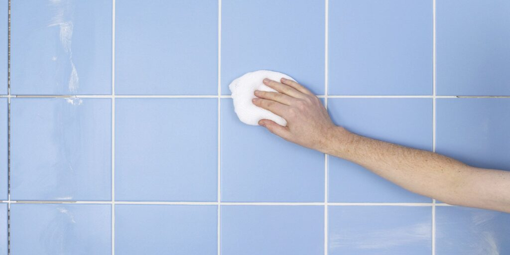Person scrubbing dirty grout tile