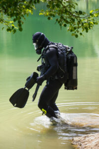 scuba diver in gear standing in the water