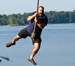 Kevin James swinging on a rope over the lake