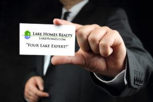 man in suit holding out a Lake Homes Realty Lake Expert business card