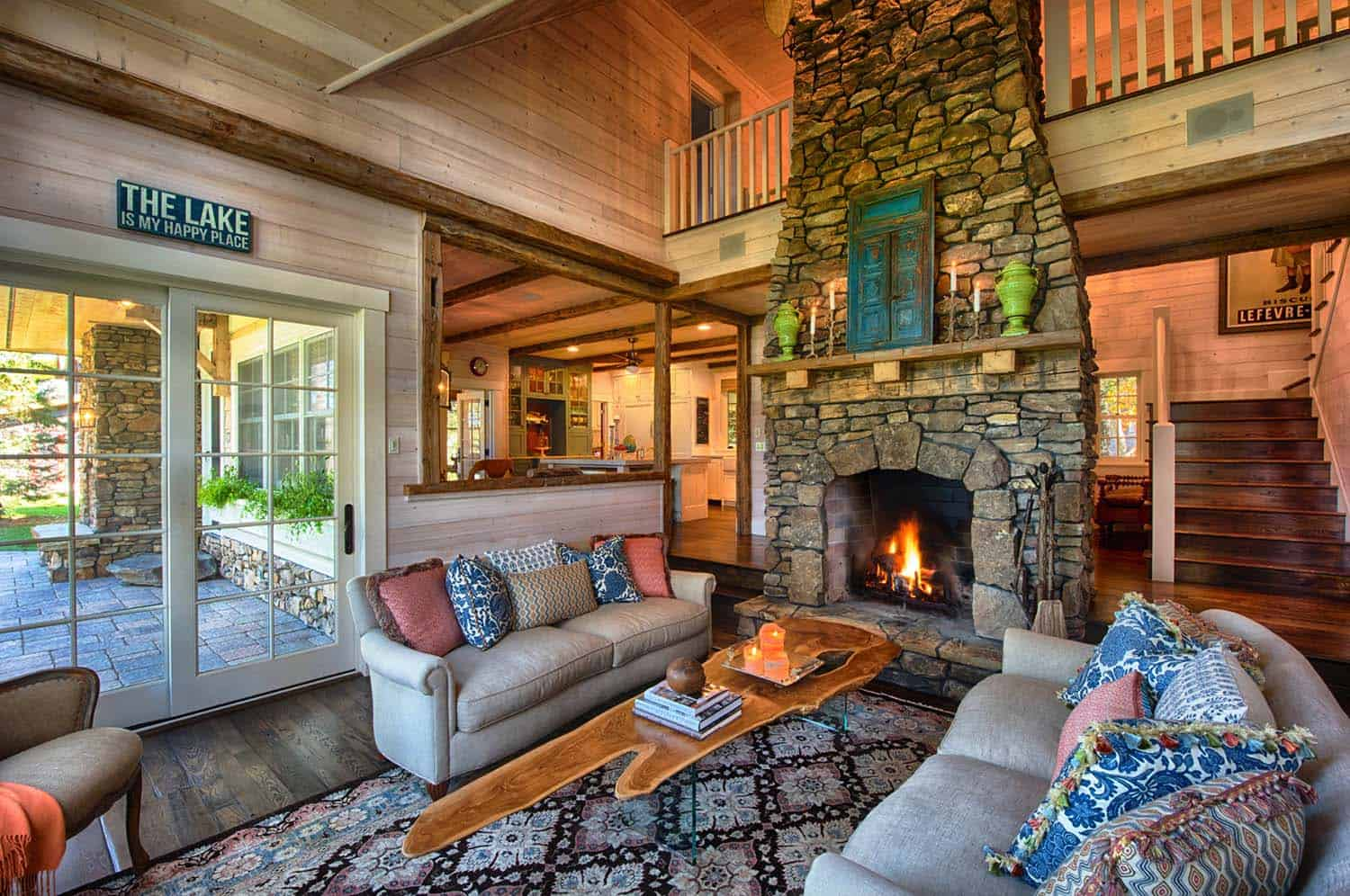 Lake home living room with burning fireplace | Lake Homes Realty