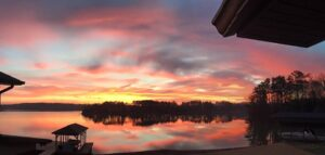 yellow, pink and grey sunset over lake from porch
