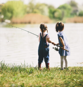 two little girls with a fishing pole on the bank of a lake