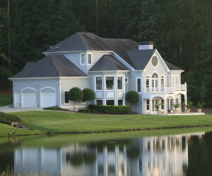 large multi-story white house with two car garage on the waterfront