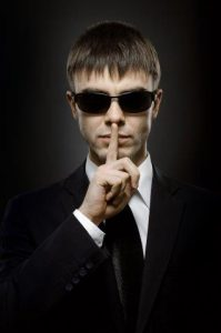 man in suit and sun glasses making the secret gesture, finger to mouth