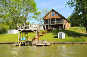wood plank multi-tier home with boat dock on water