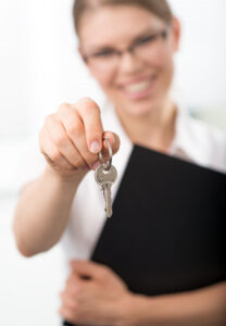 real estate agent handing over key to home