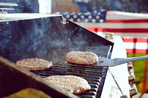 hamburgers cooking on a grill in front of American Flag