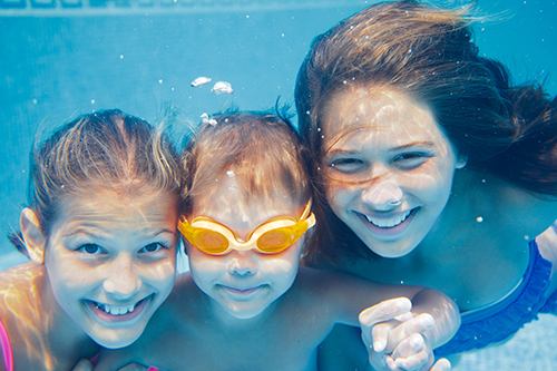 three children smiling under water