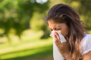 woman outside on a sunny day sneezing into a tissue