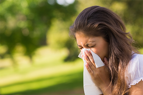 woman outside sneezing into a tissue