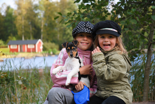 two little girls sitting by lake holding a puppy