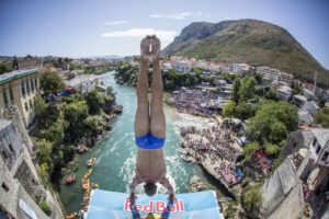 male cliff diver in handstand position on platfrom