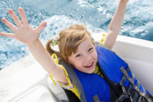 young girl in blue life jacket with hands up in boat