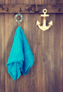 nautical style: blue towel hanging next to a decorative anchor