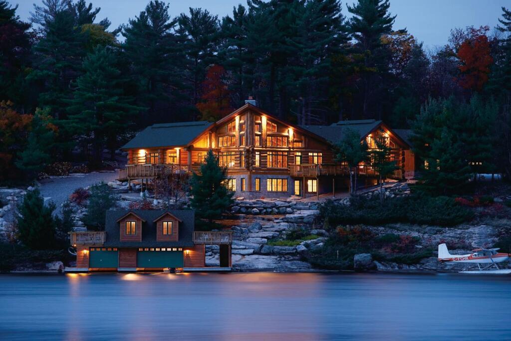 Log lake home at night