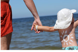 Child in swim trunks holding father's hand at the lake