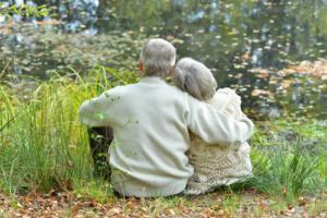 elderly couple hugging next to lake-sm
