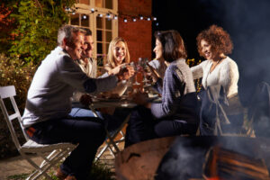 mature friends enjoying outside dinner party by fire pit