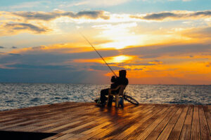 man fishing on the dock at sunset