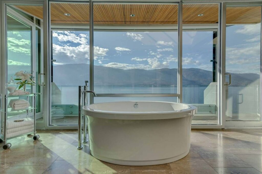 Wide bathtub with view of mountains and lake