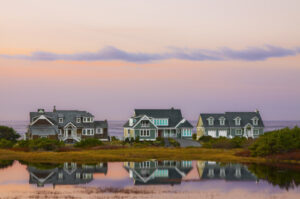 three lakefront houses at sunset