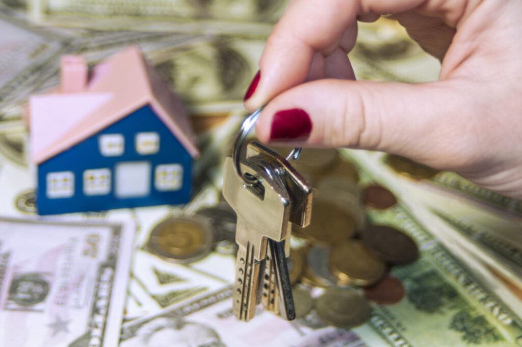 Woman holding set of keys over wooden house figurine and money