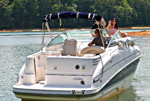 """Woman waving from deck boat. Boat description found in """"Buying the Best Boat for You."""""""