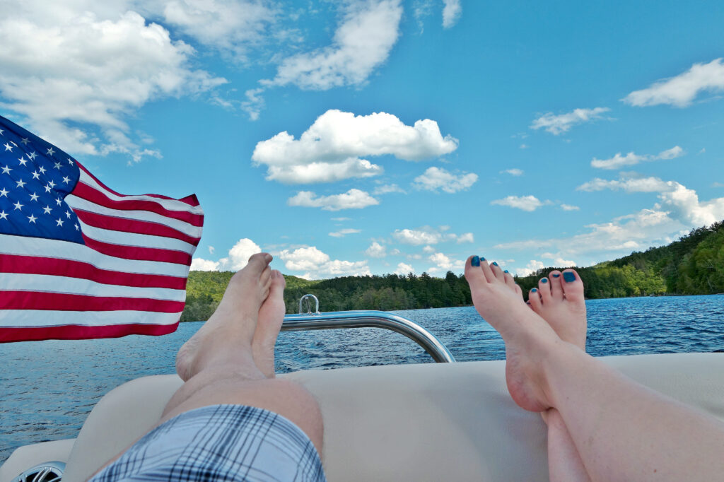 boy and girl feet hanging of the end of boat with American flag