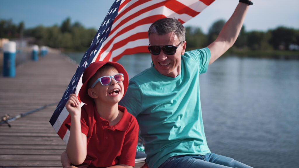 father and son on dock holding American flag