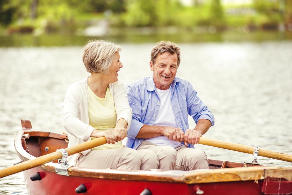 older couple enjoying lake living while rowing a boat
