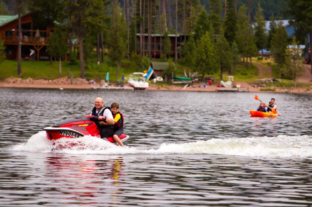 Family members jet skiing and kayaking on lake