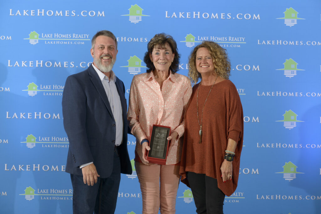 Emily Carter Morris, the winner of Lake Home Realty's Agent of the Year 2019 award, standing next to CEO Glenn Phillips and COO Doris Phillips.