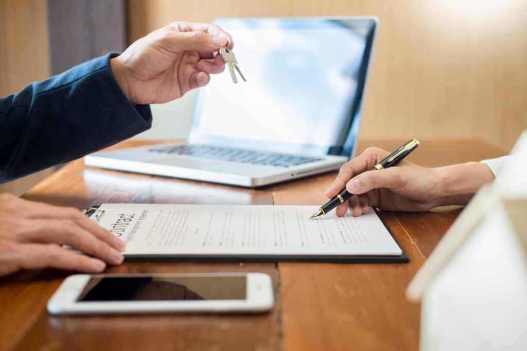 Real estate agent handing keys to person signing housing contract