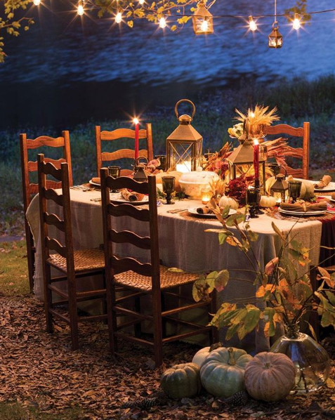Autumnal al-fresco dining by the lake illuminated by string lights and candles