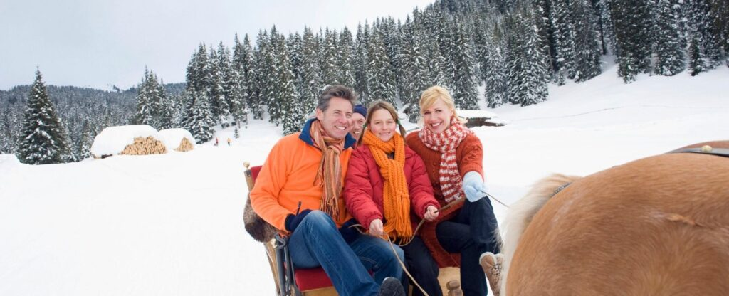 Happy family on horse drawn sleigh ride during the winter