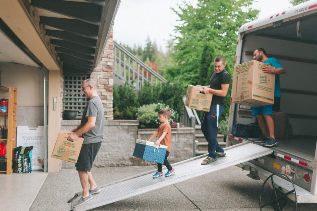 Group of three men and a little boy carrying moving boxes out of a rental truck
