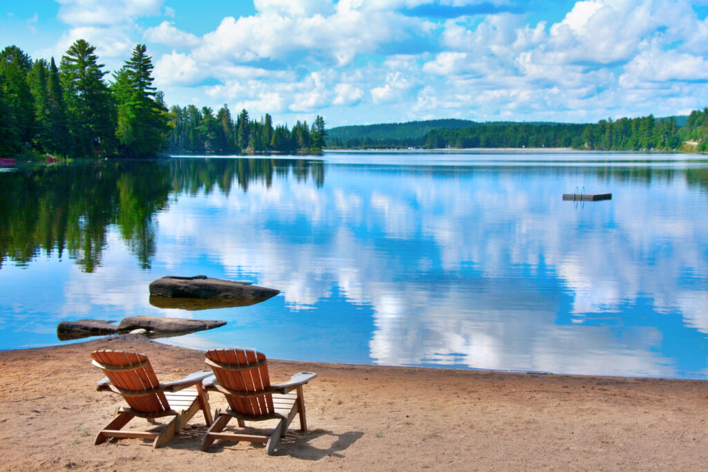 two wooden deck chairs on the shore of Douglas Lake with clouds reflecting on the water