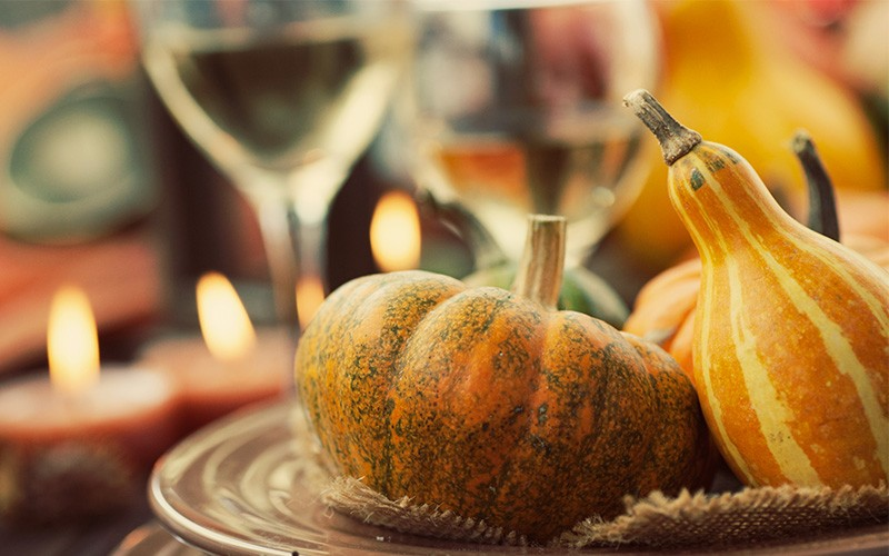 Pumpkins on table setting in front of wine glasses
