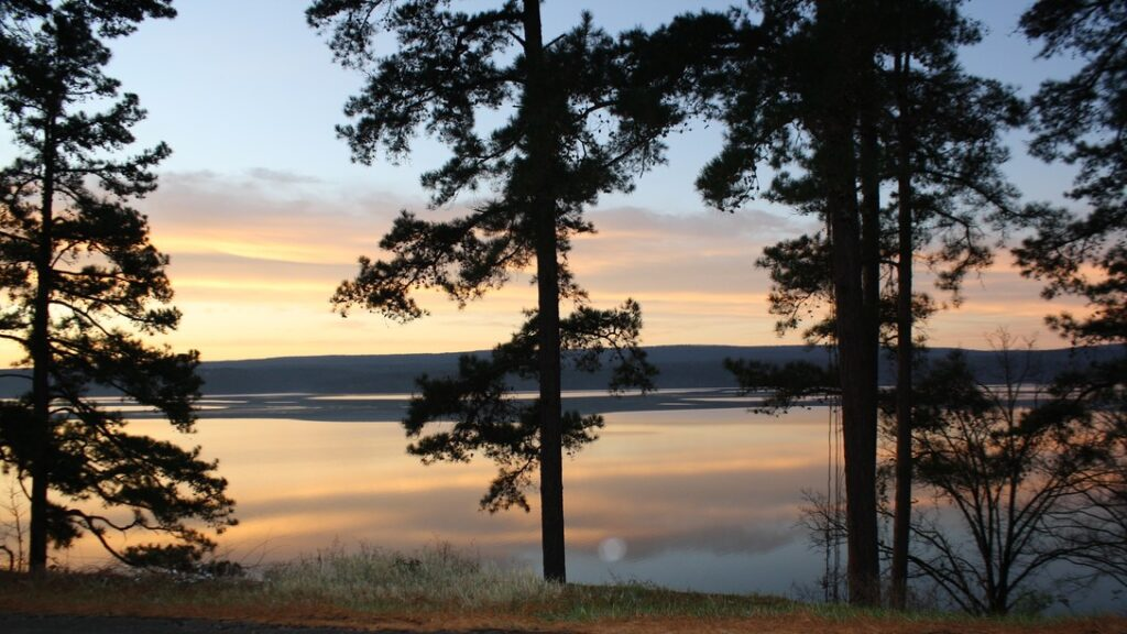 Lake with trees lining shoreline during sunset