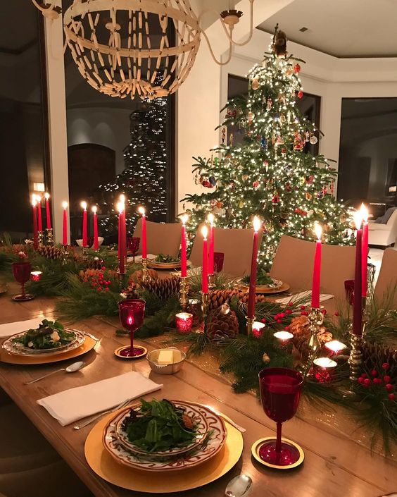 Christmas table setting during night with candles next to Christmas tree