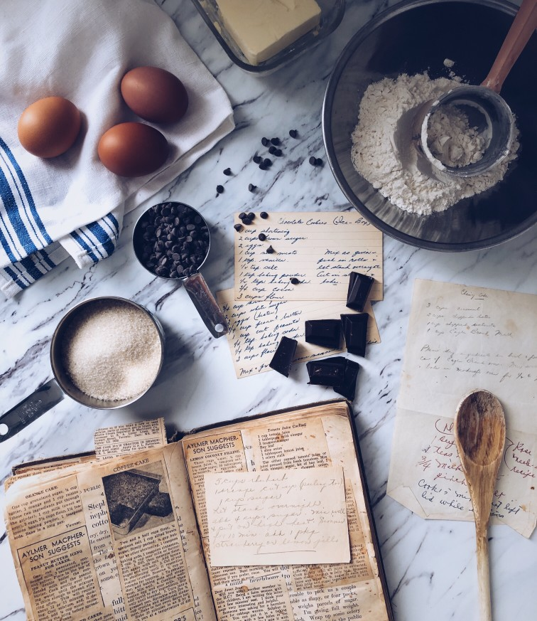 Recipe book and ingredients laid out on marble counter top