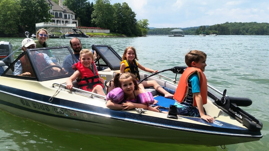 Family and children boating on lake during summer