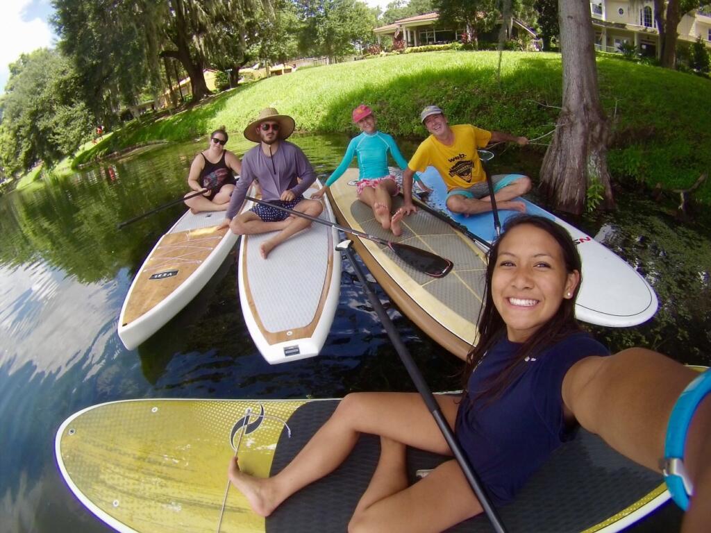 Community of lake homeowners paddleboarding together