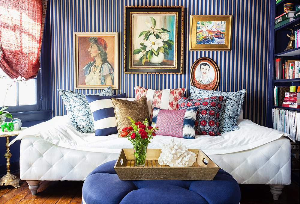 Striped navy blue wallpaper with paintings and vibrant pillows on daybed interior design trend